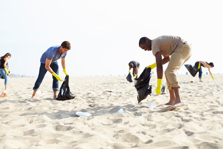 5 pessoas recolhem lixo da areia da praia