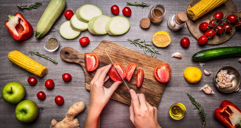 Uma bancada de cozinha com vários alimentos espalhados e uma tábua ao meio na qual alguém corta tomates