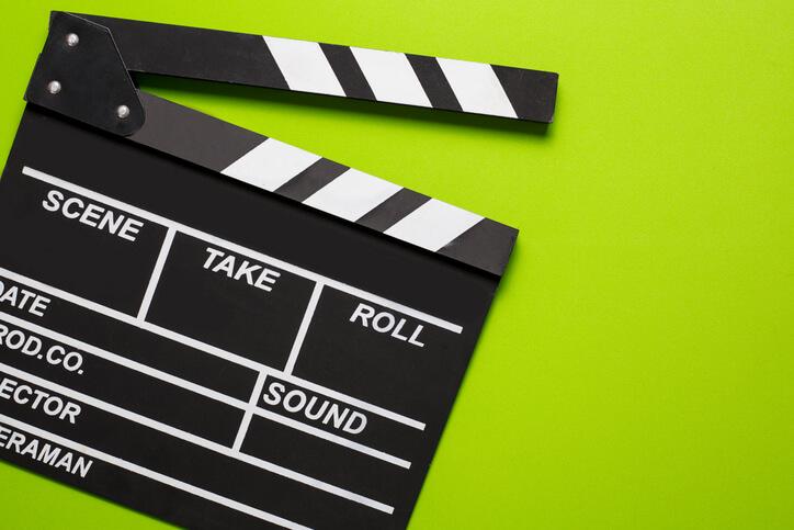 Imagem de uma claquete de cinema sobre um fundo verde