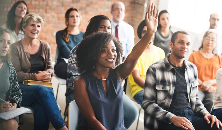 Mulher com a mão levantada em reunião de grupo de colaboradores